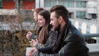 Friends have a chat. Two young men and a beautiful woman talk and laugh standing near bridge railing. Slow mo