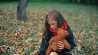funny, cheerful cute little girl playing with her teddy bear in the amazing autumn park 4k