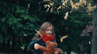 funny, cheerful cute little girl spinning with her toy, teddy bear yellow leaves fall on them from the tree slow mo