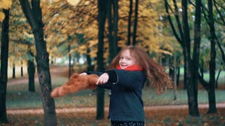 funny, cheerful cute little girl spinning with her toy, teddy bear yellow leaves fall on them from the tree slow motion