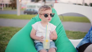 Funny little boy in a big sunglasses sitting in bean bag chair at the park in summer day. Holding a glass with straws.
