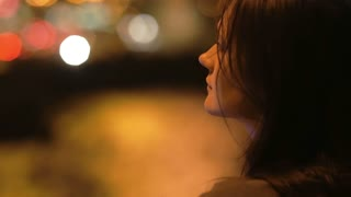 Girl at night looks in camera, smiles, turns away. Wind is blowing her hair, blurred lights, sideview, close-up, slow mo