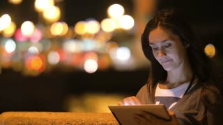 Girl in the city at night. She uses her tablet, big blurred city lights on the background. Wind blows her hair, slow mo