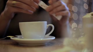 Girl pours sugar batched in the cup