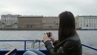 Girl sitting in a river bus on the go taking photos of architecture on a river quay. A seagull is flying around, slow mo