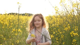 girl walking cross the field at sunset. Slow motion