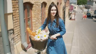 Girl walks her bike up the street with flowers in a basket as the sun shines in summertime, slow mo, stedicam shot