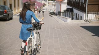 Girl wearing sunglasses walking her bike down the street with flowers in a basket, slow mo, steadicam shot