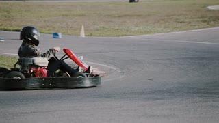 Go-kart track. Man in a kart starts moving.