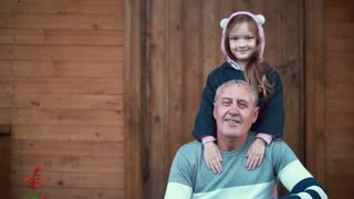 Granddaughter standing behind grandfather and hugs old man and smile. Girl bands and male kiss her hand. 4K