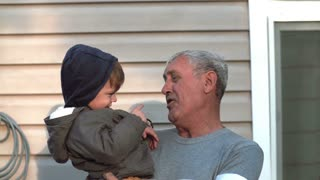 Grandfather and grandson talking, smiling, having fun, looking to camera outdoor. Old man holding on hand little boy. 4K
