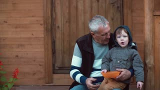 Grandson sitting on grandfather s lap and pointing with his finger. Old man kisses boy and put on the hood. 4K