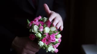 groom holds a wedding bouquet in his hands