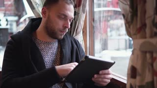 handsome bearded man using tablet computer touchscreen in cafe