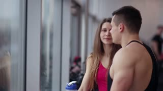 Handsome man is talking to a pretty sporty girl near the window. People are resting after workout in the gym