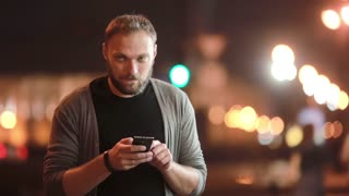 Handsome man texts, uses his smartphone and goes away. Blurred city lights in the street. Modern technology