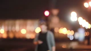 Handsome man walks, smiles, uses his smartphone and goes away. Blurred city lights in the street. Modern technology.