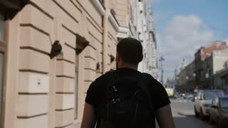 Handsome man with a beard exploring a city, wearing black backpack, looking around. Sun shines, slow mo, steadicam shot