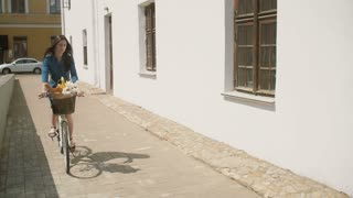 Happy beautiful brunette girl riding a bike in the street turning corner in summertime, slow mo, steadicam shot