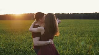 Happy beautiful lovers have fun in nature. Man and woman dance in a field at sunset in summertime. Slow mo