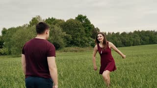 Happy couple in love have fun in the nature. Beautiful young woman jumps into her lovers arms. Slow mo, steadicam shot
