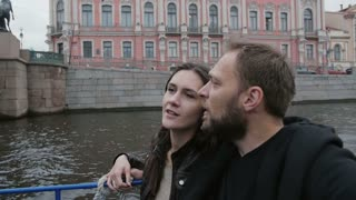 Happy couple in love on a boat tour in St Petersburg. Sightseeing, going under a bridge, light goes off and on, slow mo