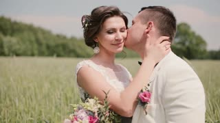 Happy couple in love share intimate moment standing in a wheat field on a wedding day. Bride and groom tenderly kissing.