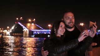 Happy couple in love taking selfie. A movable Palace Bridge St. Petersburg at the background. City illumination at night