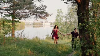 Happy couple walk on river bank, hold hands. Forest in summertime. Beautiful view of nature. Slow mo, steadicam shot