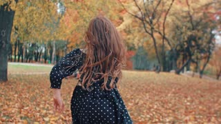 happy cute little girl runs to her mother and brother through amazing autumn alley in the park slow mo