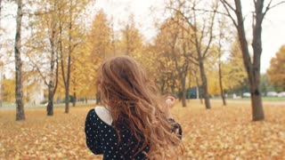 happy cute little girl with curly hair, in dress with polka dots runing through the autumn alley in the park slow mo