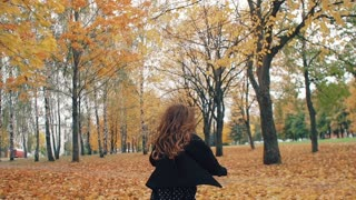 happy cute little girl with curly hair runing through the autumn alley in the park slow mo
