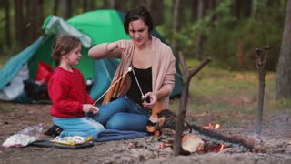 Happy family having great time together in the nature. Mom teaches her daughter to cook marshmallows on open fire.