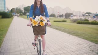 Happy girl in a dress cycling and exploring the city, slow mo, steadicam shot