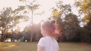 Happy little girl blows kisses in front of camera in the nature. Sunset light, rays of sun shine through trees. Slow mo