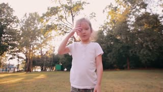 Happy little girl cheerfully jumps, blows kisses in front of camera in the nature. Beautiful sunset light. Slow mo
