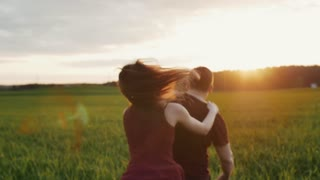 Happy lovers joyfully run in a field in nature. Couple having fun. Sunset light shines. Backview slow mo, steadicam shot