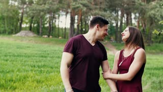 Happy lovers walking in a forest, spending great time together, talking and laughing.