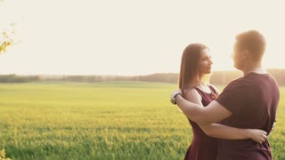 Happy man and woman in love stand in a field at sunset. They embrace and kiss, gently touch each other. Slow mo