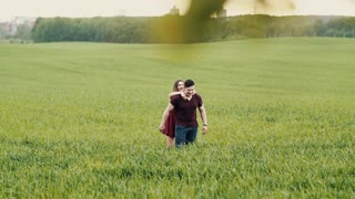 Happy moment between two lovers. Smiling brunette woman jumps on her lovers back, he carries her in a field. Slow mo