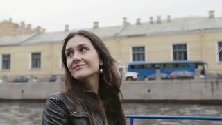 Happy pretty young woman having a tour on a boat. Exploring St Petersburg. Brunette girl sightseeing, slow mo