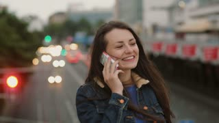 happy, smiling pretty woman talking on the phone standing on the bridge and. Wind blows her hair. 4K