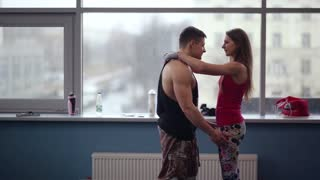 Happy sporty couple rejoicing after a training in the gym. Man lifts his lover and swirls around, they kiss.