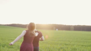 Happy woman chases her man running in field at sunset. She jumps on his back. Backview, slow mo, steadicam shot