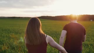 Happy woman chases her man running in field at sunset. Womans hair sway in the wind. Backview, slow mo, steadicam shot