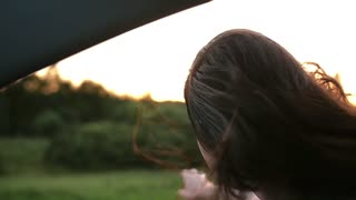 Happy woman smiles, enjoys traveling by car. She reaches her arm through the window of a car. Wind blows hair. Slow mo