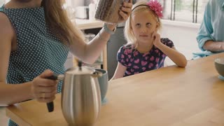 Happy young family: mom, dad and their daughter having breakfast at the kitchen table. Slow motion, steadicam shot