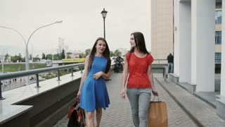 Happy young girls friends walking after shopping with purchases in bags, talking discuss something slow mo stedicam shot