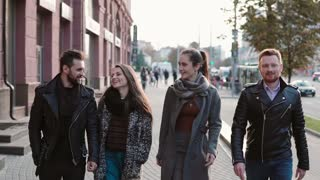 Happy young people cheerfully walking near road in city centre. Friends walk, chat, laugh. Steadicam shot, slow mo