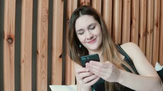 Happy young woman using smartphone lying on sofa at home and smiling. Girl texting on the phone resting in living room.